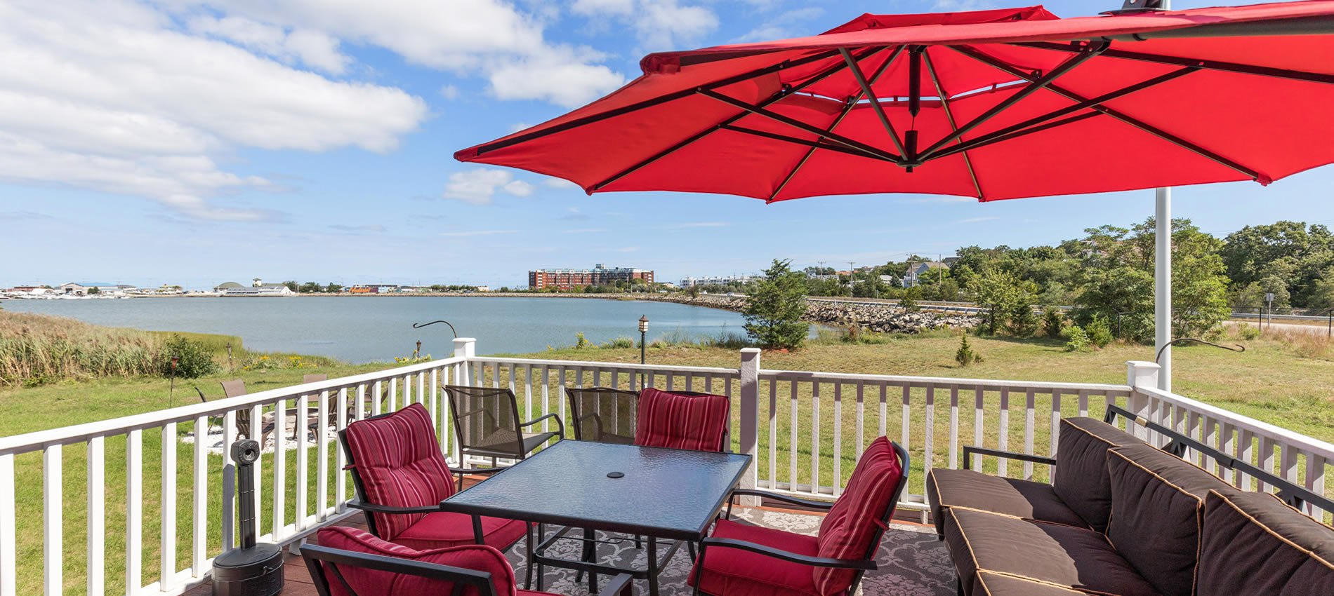 beacon waterfront inn in hull ma deck and chairs with umbrella overlooking water