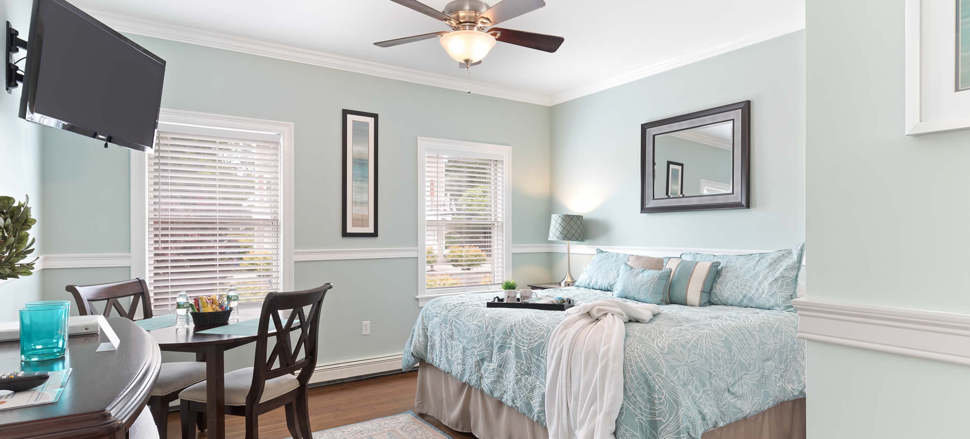 nantasket beach boutique hotel guest room with bed table robe and ceiling fan